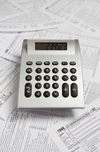 A calculator on top of tax return forms