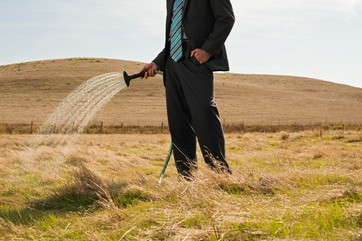 Man sprinkling water on dry grass